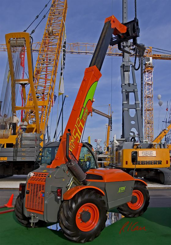 Construction material handling: XTreme XRM519 telescoping boom forklift. Liebherr HS 895 HD Litronic crane is background left, and Liebherr LRB piling and drilling rig is background right. CONEXPO, Las Vegas, Nevada, March 15-10, 2005.