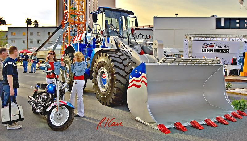 Earthmoving, aggregate construction: Liebherr 580 2 plus 2, 5 m3 bucket, wheeled front end loader and two dollies and a cycle in patriotic colors. CONEXPO, Las Vegas, Nevada, March 15-19, 2005.