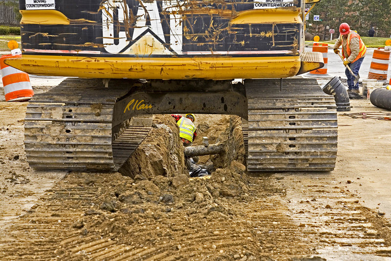 Trench construction, safety: Caterpillar 3128 crawler mounted backhoe straddles trench for underground pipe. Worker in trench is fine grading/cleaning trench with shovel. Workers standing in 8 ft deep trench have no support against sidewall collapse. Safety and laws require the trench walls to be supported or sloped back at depths greater than 5 ft. Michigan 2006