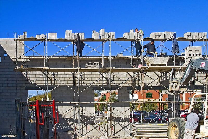 "Masonry construction safety, fall hazard: Two bricklayers stand on wood plank working platform 20 ft above ground with no fall protection. The wall currently extends only 8"" above the platform on which they stand. As they place mortar (as bricklayer on left is doing) and concrete block, they are exposed to a 20 ft fall. Bricklayer at right is getting his trowel out of his tool bag, to join the other bricklayer in laying block. <br /> <br /> All work/ material platforms supported by top frame of tubular scaffold, except at mortar box and concrete block landing areas, have steel cross-bracing. Guardrails with toprails and midrails are required by OSHA. Cross-bracing may serve as toprail or midrail, if crossing point is 20"" to 30"" above work platform for midrail or 38"" to 48"" above work platform for a toprail. The cross-bracing on this project can serve as toprail, but a mid rail is still required. Ann Arbor, 2004."