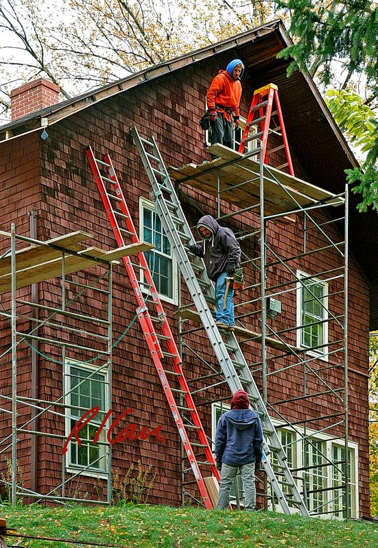 Fall hazard, unsafe scaffold/ladder, construction safety: Six foot stepladder stands on unguarded scaffold platform 20 feet above ground. Therefore, worker(s) worked on stepladder at least 23 feet above ground without using fall protection. Scaffold should have standard guardrail on outside three sides, except for break for access. Ladder should be tied off at top to scaffold. Worker on scaffold platform next folds ladder and hands it to worker on ladder, who hands it to worker on ground. Ann Arbor, Michigan 2005