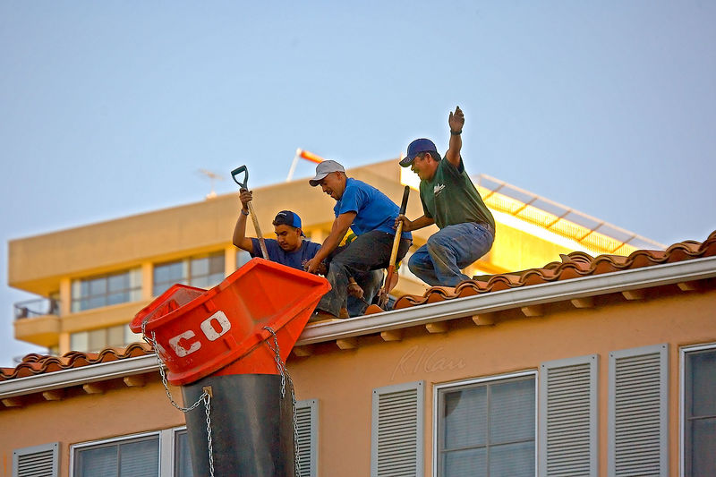 Construction safety, roof construction, demolition: Four roofers at edge of roof, without fall protection, manhandle lifting and tying off flared top of trash chute with which to funnel old roofing material into dump truck for disposal. The crew is using two pitch forks (hand tools for roof demolition) to pry top flared part of chute over and above roof edge and gutter. Worker on right lost his balance an instant before this photo was taken, and in photo he is raising left arm and sitting back with grimace on his face, which saved him from pitching over roof edge and falling two floors. Of course, workers return next day to demolish roof , including near edge, and walk to edge of roof to drop debris into chute. They should all be wearing body harnesses, with lanyards tied back with safety line to a secure support near center of roof. California, 2006.