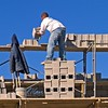 Masonry construction safety, fall hazard: Laborer/ hod carrier stands on top of 6 ft high unstable stack of concrete block and 19 ft above ground, leaning out and stacking heavy blocks, with no fall protection from safety line or guardrail. Ann Arbor, 2004.
