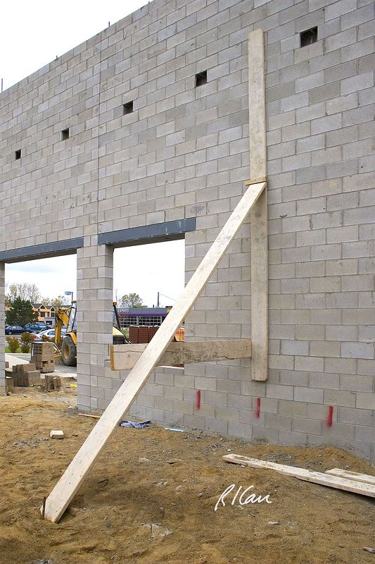 Masonry construction safety bracing: Typical inadequate and unsafe bracing of concrete block walls against wind, on interior of this building: (1) Single nail connections between 2x10 plank members cannot transfer anticipated loads. (2) Stake in soil (#6 rebar here) cannot support anticipated wind load. (3) Lack of connection between vertical plank and masonry prevents transfer of anticipated wind load to bracing system. Ann Arbor, 2004.