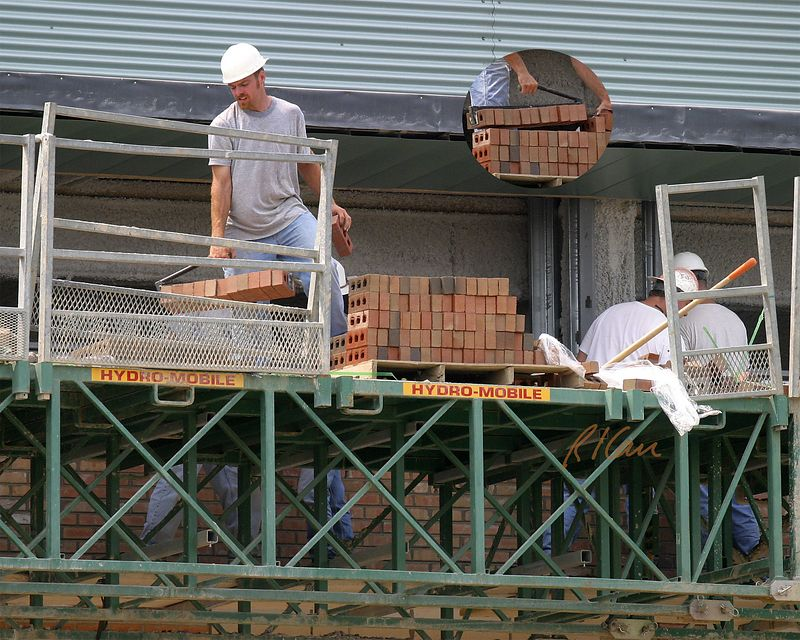 Masonry construction safety: Laborer transporting brick from stacked brick on pallet to position next to bricklayers. Fall protection is not complete, because a section of guardrail moved (it is leaned against guardrail to our left of opening) to allow forklift to place brick pallet on material platform has not been replaced. Ann Arbor, 2004.