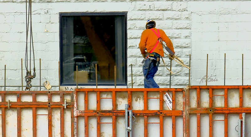 Construction safety, fall protection: Worker walks along top of concrete basement wall more than 20 feet above the ground, among reinforcing bar tripping hazards, without any fall protection. He carries two safety lanyards and hooks, attached to full body harness and hooked temporarily at his right chest. Instead of protecting him, he repeatedly has them loop over extended rebars, which adds to the hazard. Michigan 2006.