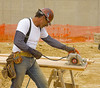 Carpentry, concrete formwork construction: Worker uses rotary saw to cut plywood to provide formwork for cast-in-place reinforced concrete walls to be erected at the new high school in Ann Arbor, Michigan, May 2006