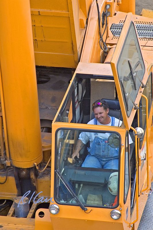 Steel construction: Operating engineer operates Grove TM9150 truck mounted, 150 ton hydraulic crane lifting heavy structural steel sections.  UCLA, Los Angeles, CA, 2004.
