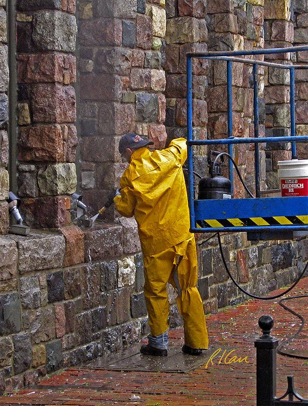 Worker cleans rock masonry with low pressure spray of masonry restorer. Pressure is from the black hand pumped pressure pump on the work platform.  Gandy Dancer Restaurant, Ann Arbor, 2003.
