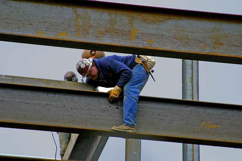 Ironworkers bolt wide flange beam in position in erecting structural steel for YMCA, Ann Arbor, 2004
