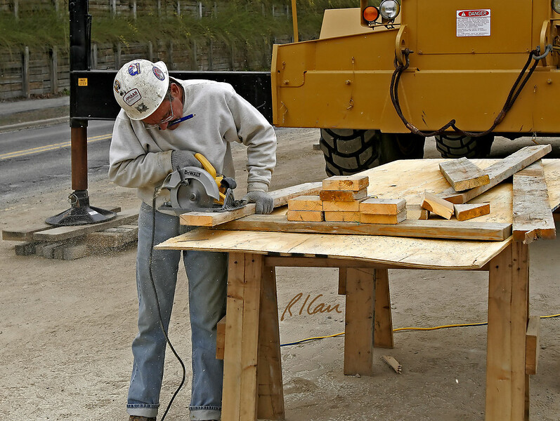 """Retaining wall construction:  Worker uses DeWalt rotary saw to cut short pieces of 2"""" x 8"""" dimension lumber to be blocking to position precast concrete panels against road side of structural steel H-section soldier beams. Huron Parkway South of Huron River, Ann Arbor, MI, 2005."""
