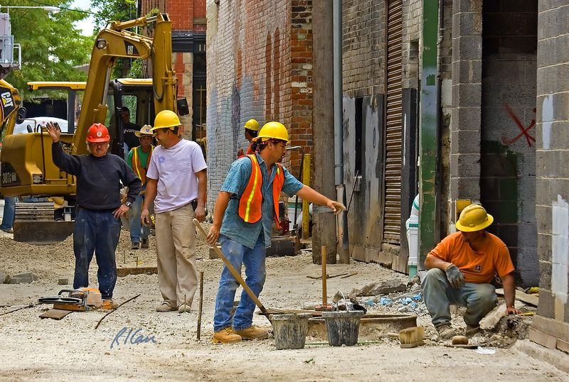General, masonry, construction: Communication within busy construction crews. Two workers in right foreground discuss their work on manhole and rear entrance to building. Worker at left is talking dramatically to his foreman. Worker in center rear gives directions to backhoe operator. Alley between Washington and Liberty, 1/2 block West of Main, Ann Arbor, Michigan, 2005.