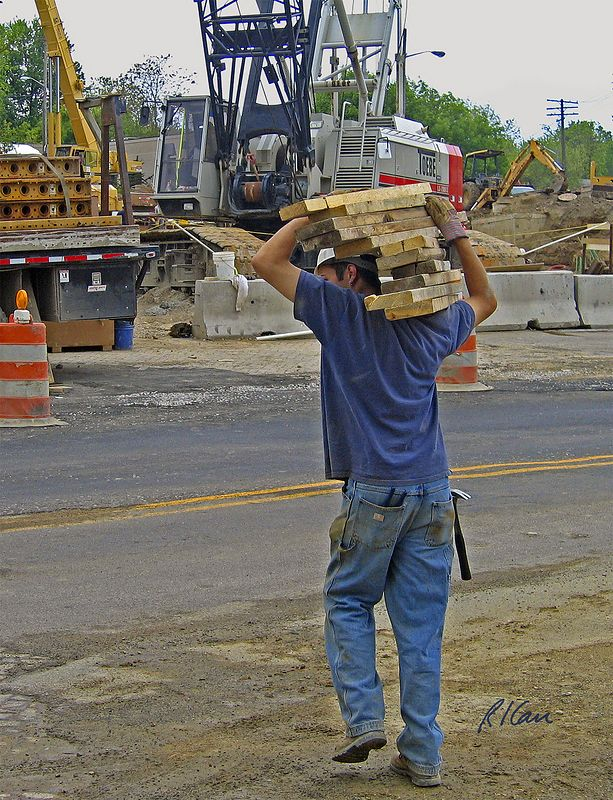 Worker carries short sections of 2x8 lumber on his shoulder, crossing Depot Street. Broadway Bridge, Ann Arbor, 2003.