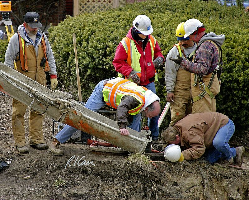 Underground construction: Crew inspects, discusses conditions in man hole, at side of excavation. Concrete readymix truck chute is ready to place concrete. Broadway Bridge, Ann Arbor, 2003.