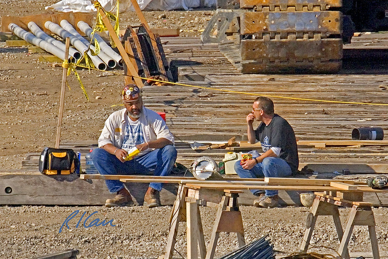 Construction: Two structural steel erection ironworkers at lunch break. They are sitting on one of the timbers that provides a good base for the tracked crane behind them. In the foreground is a small carpenters fabrication shop, consisting of two sawhorses and powered hand tools. Cardiovascular Care, University of Michigan, Ann Arbor, March, 2004.