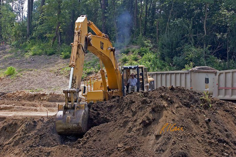 Earthmoving construction: Caterpillar 350 crawler mounted hydraulic backhoe loading soil onto Peterbilt tandem rear dumping trucks that haul off site. Dixboro Bridge, Ann Arbor, 2004.