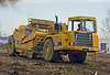Soil, earth construction: Caterpillar 613C elevating/self-loading scraper, 11 CY capacity, 175 hp, is moving earth to level land to a more even grade for construction of condominiums. Scraper is making a loading pass, with its bowl cutting edge lowered to scrape up earth and elevating paddle buckets rotating to pick up soil against bowl edge and elevate it to fall into the bowl. Ann Arbor, Michigan 2006.
