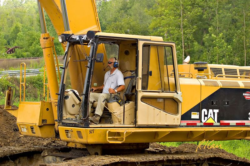 Earthmoving construction: Operating Engineer operates Caterpillar 350 crawler mounted hydraulic backhoe loading soil onto tandem rear dumping trucks. Dixboro Bridge, Ann Arbor, 2004.