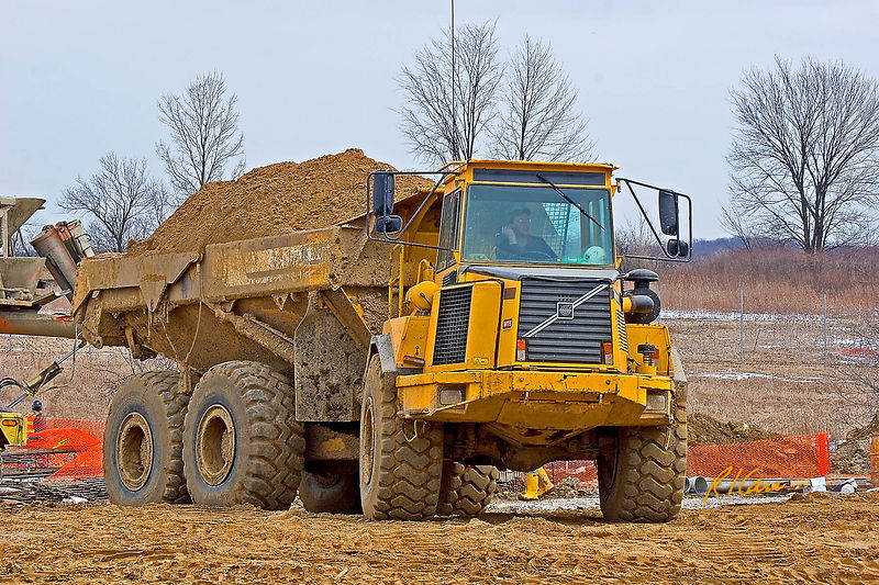 Soil, earthmoving construction: Volvo A25C 6x6 articulated off-road rear-dump hauler carries full load of soil. Articulation provides a powered vertical hinge between tractor and trailer for tight turns. It weighs 18 tons and carries 22.5 ton payload. East Ann Arbor Health Center, Ann Arbor, Michigan 2005.