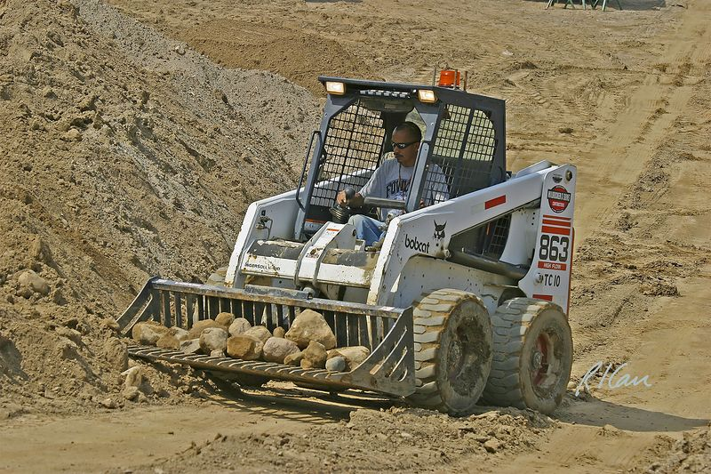 Earth moving construction: Bobcat 863 skid-steer tractor with stone separating blade/bucket lifts and sifts soil to extract and separate stones. Dixboro Bridge, Ann Arbor, MI, 2004.