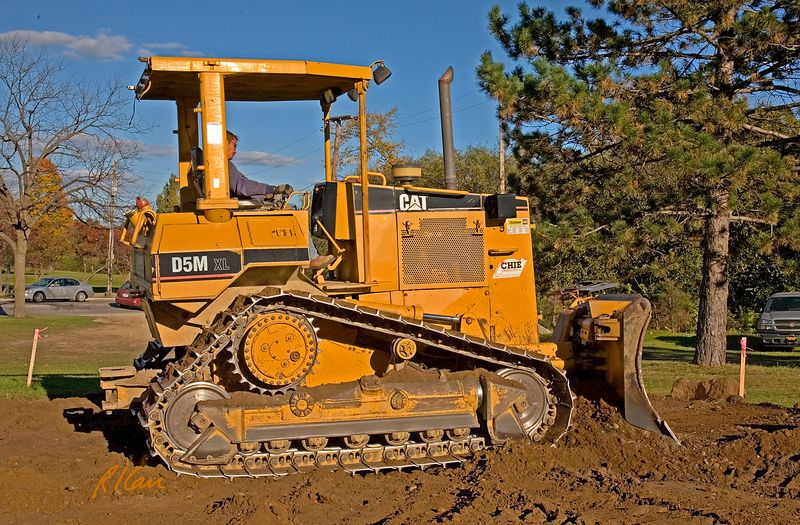 Soil construction, earth moving: Caterpillar D5M 110 hp track mounted bull dozer backs up using backside of dozer blade to position the soil for front end loader to pick it up and deliver it to another part of project. Huron Parkway, Ann Arbor, Michigan 2005.