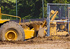 Caterpillar 621F wheel-tractor scraper is pushed by Cat D6R bull dozer. Photo shows detailed view of dozer blade pushing on rear push block of scraper.  The Courtyards private dormitory, North Campus, University of Michigan, Ann Arbor, Michigan. 2007.