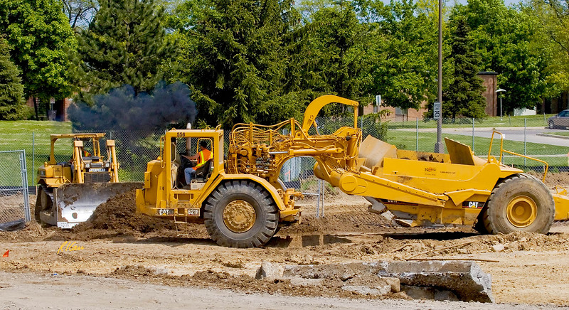 Caterpillar 621F wheel-tractor scraper returns to cut area after dumping previous load at fill area. Cat D6R bull dozer is rough grading earth slope on which scraper became hung up going uphill with last load. The Courtyards private dormitory, North Campus, University of Michigan, Ann Arbor, Michigan. 2007.