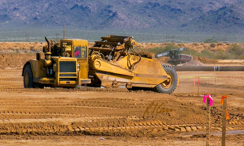 Caterpillar 623B self elevating scraper doing cut and fill to prepare land for development between Phoenix and Tucson, Arizona. Scraper has filled its bowl doing cut and is traveling with bowl raised to fill area to dump its bowl. November, 2006.