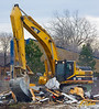 Caterpillar 345B backhoe heaps demolition debris with its grappler bucket and tracks back and forth on top of the debris to compact its volume before loading it into a debris dumpster to be hauled away. Washtenaw near Huron Parkway, Ann Arbor, Michigan. January, 2007.