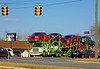 Volvo truck tractor pulls automatically adjustable vehicle carrier loaded with 8 cars and pickups. Carpenter Road and Michigan Avenue/US 12, Ann Arbor, Michigan, March 2007.