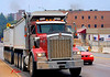 Truck, hauling equipment, earthmoving construction: Kenworth truck tractor pulls two tandem trailers to be loaded with earth excavated for a commercial building basement/foundation. Huron Street, Ann Arbor, Michigan, August 2006.