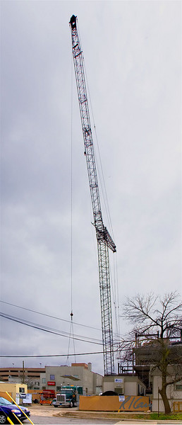 Manitowoc crawler mounted lattice boom crane with luffing jib lifts hollow core precast concrete floor deck slab off flatbed trailer powered by Peterbilt semi tractor. Ashley Terrace, Ann Arbor, Michigan April, 2007.