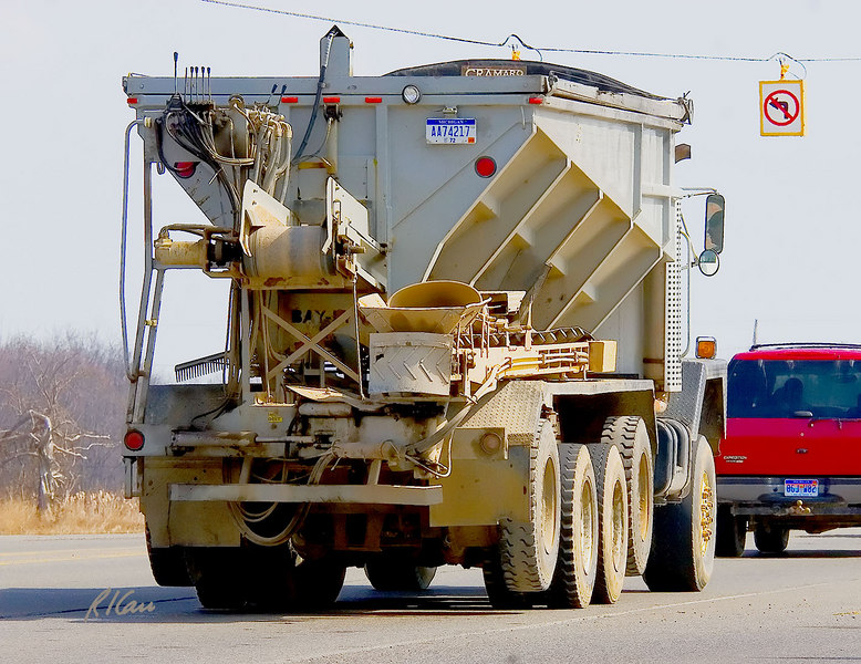 Bay Lynx Multicat stone/soil spreader mounted on International Paystar 5000 truck chassis. Conveyor feeds from bottom of truck bed and dumps stone/soil onto spreader conveyor that extends from rear. (Spreader conveyor is here rotated forward, on right side, for traveling. Spreader conveyor accurately throws stone/soil a distance and direction controlled by speed and direction of the spreader conveyor. Spreader conveyor controls are at top left of truck rear. Plymouth Road, Ann Arbor, Michigan. March 2007.