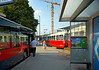 Bus and trolleys wait for passengers at Praterstern train station. In background is tower crane for major construction at station. Vienna, Austria. July, 2006.