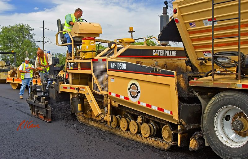 Asphalt paving construction: Caterpillar AP-1050B hot mix asphalt paving machine places asphalt pavement. The AP-1050B has 10 ft basic screed, will pave a maximum width = 30 ft, has 15 ton hopper, and weighs 42,500 lb. It is receiving the hot mix asphalt concrete from a rear-conveyor hot asphalt delivery trailer. Eisenhower Parkway, Ann Arbor, Michigan 2005.