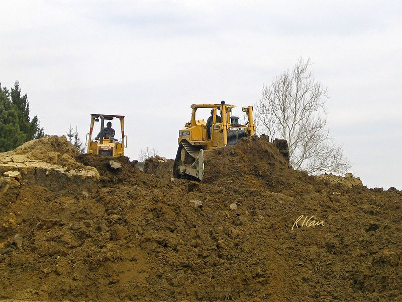 Earth Construction: Caterpillar D8R (front) and D4C bulldozers move soil together. North Campus construction, University of Michigan, Ann Arbor, 2004.