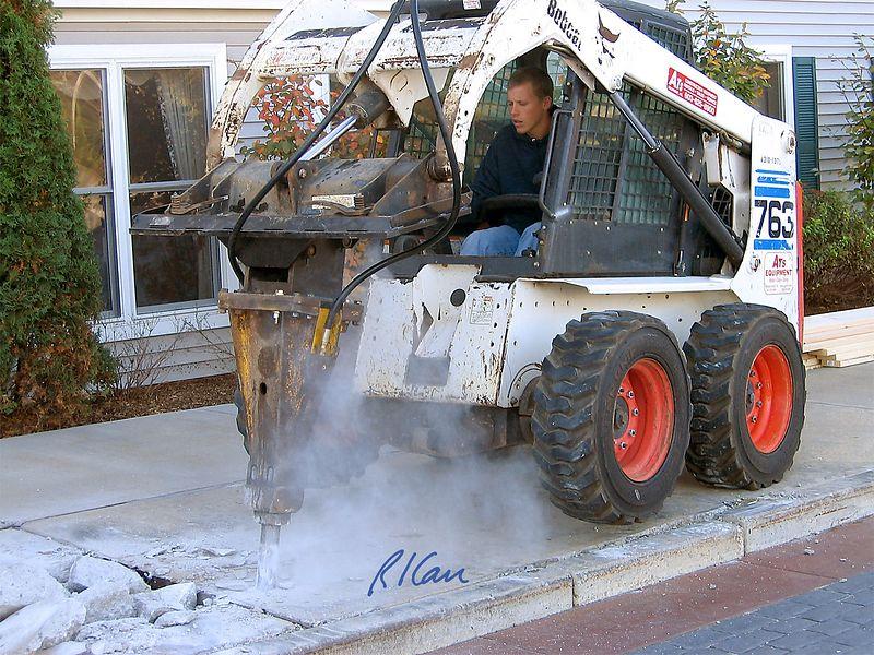 Bobcat 763 skid steer tractor uses pavement breaker attachment to break up concrete sidewalk.