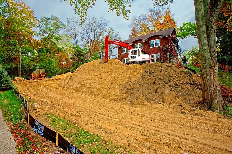Earthmoving construction, rough grading:Link-Belt LS-2650 crawler mounted, hydraulic backhoe excavator sits on soil pile it created, looking down on its excavated driveway and garage foundation. Residence in background is receiving exterior repairs. Note the geotextile mud dams at lower left that limit runoff from site to adjacent property. Ann Arbor, Michigan October 2005.