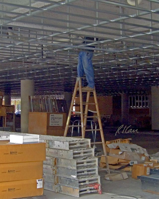 Construction Stepladder: Person working off stepladder. It is unsafe and illegal to stand on the top step (far side) of a stepladder or on the ladder's back bracing (near side). This worker is doing both. Ann Arbor, 2004.