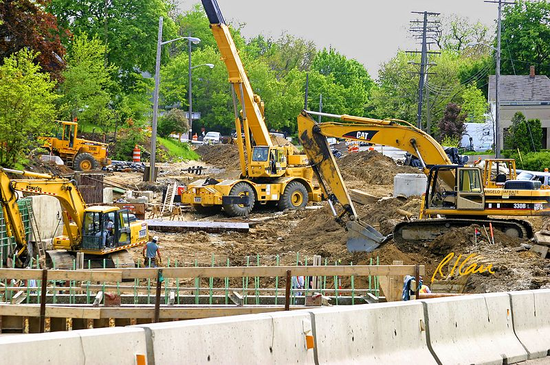 Construction backhoes, hydraulic crane, front end loader in tight work area perform earth moving and concrete foundation construction. Broadway Bridge, Ann Arbor, 2003.