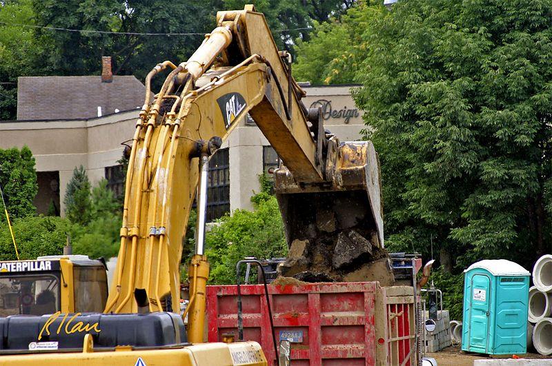 Asphalt construction: Caterpillar 330B crawler mounted hydraulic backhoe crowds and picks up broken asphalt pavement debris from Broadway and loads it into dump trucks.  Broadway Bridge, Ann Arbor, 2003.