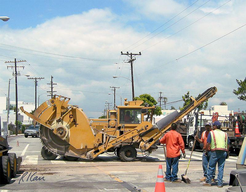 Asphalt construction: Asphalt wheel saw cuts groove in asphalt pavement, and conveyor loads waste asphalt into truck.