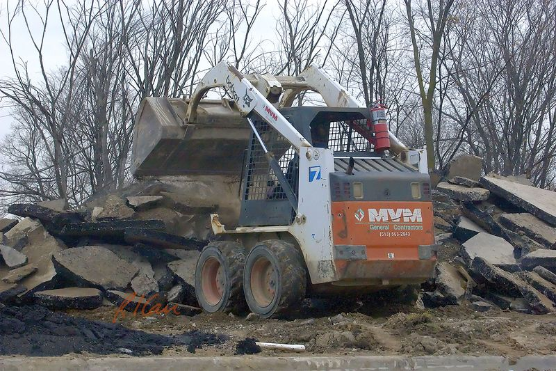 Construction demolition and recycling: Bobcat skid steer tractor with loader attachment dumps asphalt pavement debris into pile to be reclaimed. Sams Club, Ann Arbor, 2004
