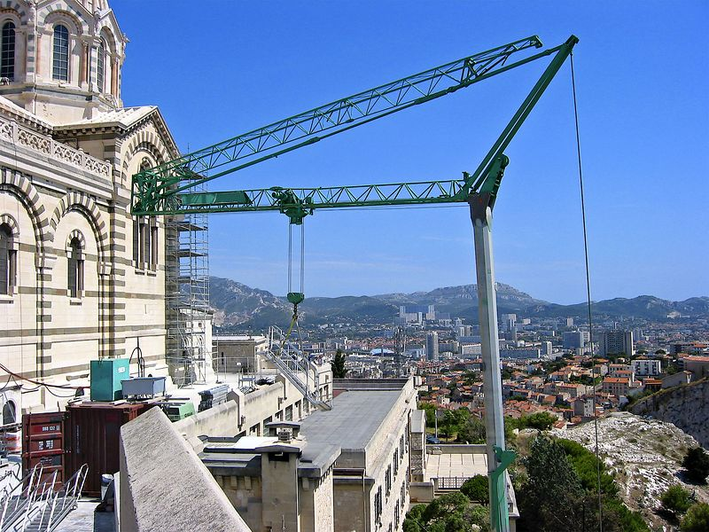 Construction crane: Driving Potain compact self-erecting tower crane on Cathedral de la Major in Marseilles, France. Second section of boom is folded back.
