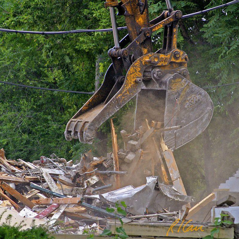 Building construction demolition. Komatsu backhoe grapple releases building demolition debris. YMCA, Ann Arbor, 2003