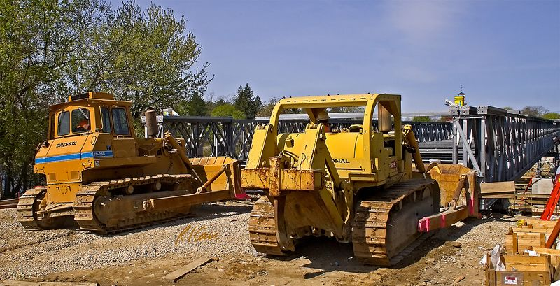 Bridge construction, steel construction: An International dozer and a Dressta dozer both push on the erection end of the Mabey Bridge that will temporarily carry Route 113 vehicle traffic to allow rehabilitatrion of the adjacent steel truss bridge over the Merrimack River. Additional prefab panels will then be erected to lengthen the bridge, which then can  be pushed out further. Cycle continues until bridge reaches west shore of Merrimack. Tyngsborough, MA 2005.