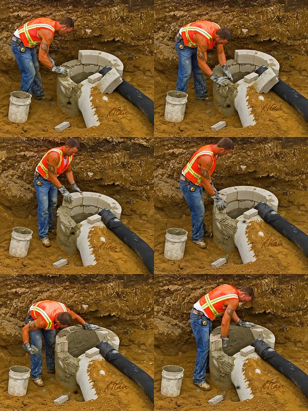 Sewer construction, masonry construction: Worker builds drain basin for storm sewer using portland cement mortar and curved concrete blocks. Mortar is mixed in mixer and transported in white plastic bucket (lower left). Worker first uses his hands to take mortar from bucket and place it on concrete block. He then places concrete blocks in mortar. Lastly, he spreads mortar over the inside surface of the drainage basin. A drain basin is where storm water draining from stree (such as through corrugated black plastic flexible tubing) flows into the main storm sewer. Huron Parkway, Ann Arbor, Michigan, 2005.