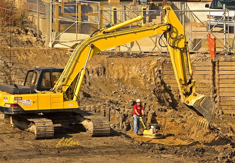 Earthmoving construction: Crawler mounted hydraulic backhoe reaches to excavate earth for basement. Laborer operates vibratory soil compaction machine in area recently excavated, beyond backhoe. In right background, soil is supported by timber breastboards. Breastboards are supported by structural steel H shape soldier beams, which were themselves driven as piles deeply into the soil, below bottom of basement. Cardiovascular Center, University of Michigan Hospital, Ann Arbor, 2004.