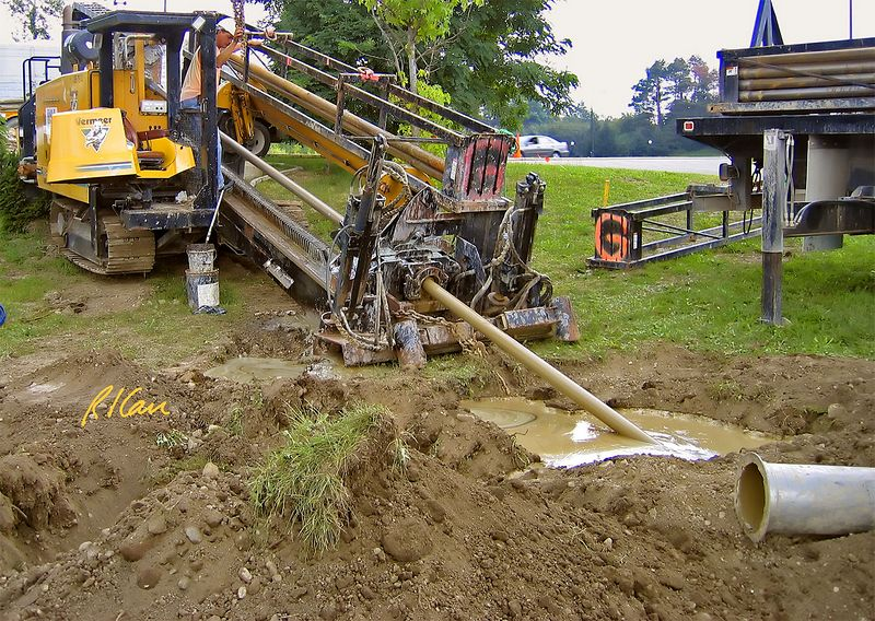 Underground construction: Vermeer D80x120 Navigator horizontal directional drill (HDD) engine in rear driving drill stem into mud hole drilling horizontally next to intramural athletic fields at University of Michigan, Ann Arbor, 2004.