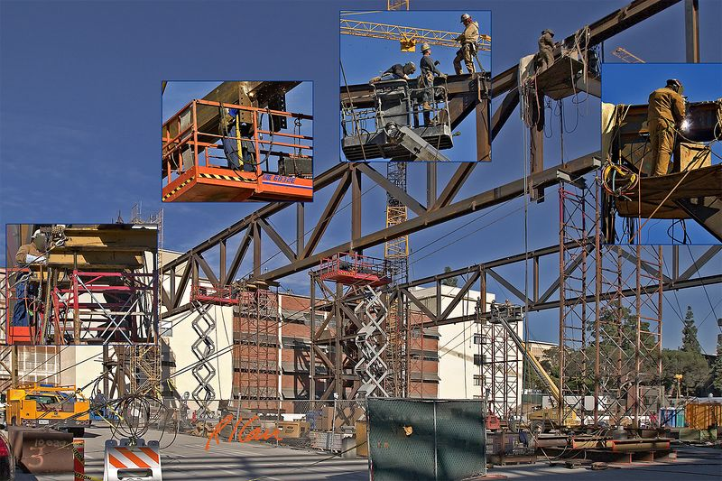 Steel construction: Structural ironworker crews assemble shop fabricated large, high steel truss components into deep, longspan truss. All workers have fall protection: Support from personnel lift, body harness with safety lanyard attached by sliding clip to top flange of truss or other truss location.  UCLA, Los Angeles, CA, 2004.
